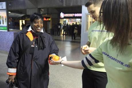 Erin Sullivan (right), developing coordinator for Samaritans, hands an orange to Dina Alen, an Orange Line supervisor, at Back Bay station. Below: Sullivan (left) with Roberta Hurtig, executive director of Samaritans.